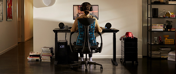 A person sits in an ergonomic gaming set up