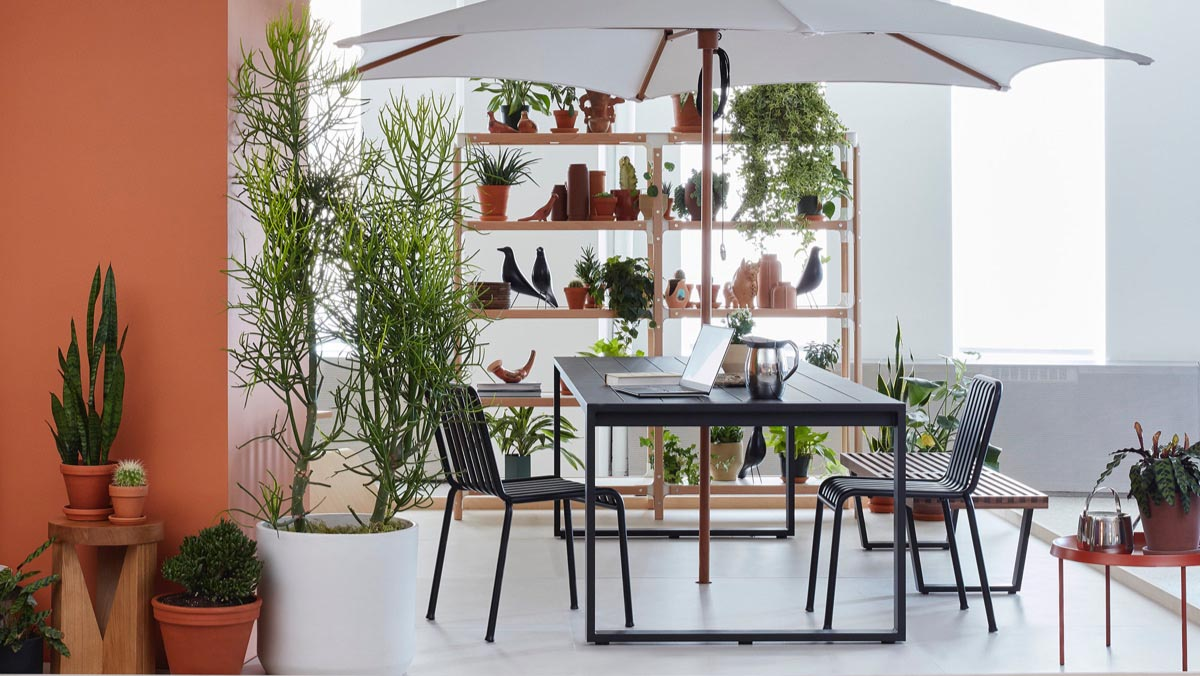 A communal outdoor patio setting with dark gray Eos Rectangular Table and Palissade Chairs, a Nelson Platform Bench, a Magis Steelwood Shelving System, and a variety of potted plants placed throughout.